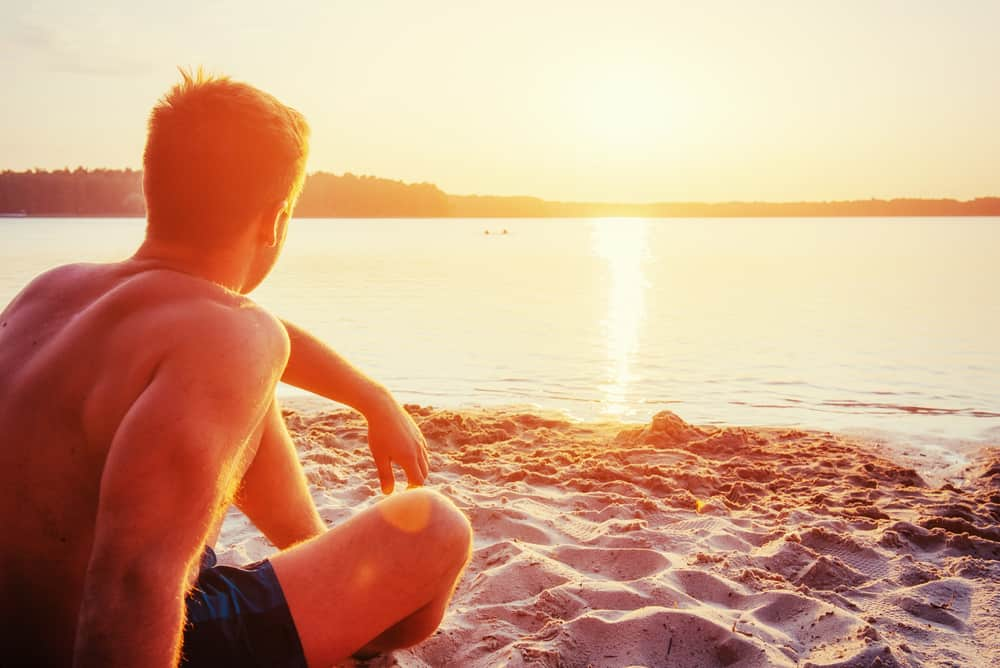 A man sits quietly on the beach reviewing his coping skills to cope with relapse and recovery.